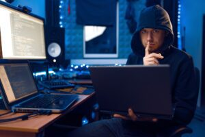 Hacker in hood shows thumbs up, network criminal