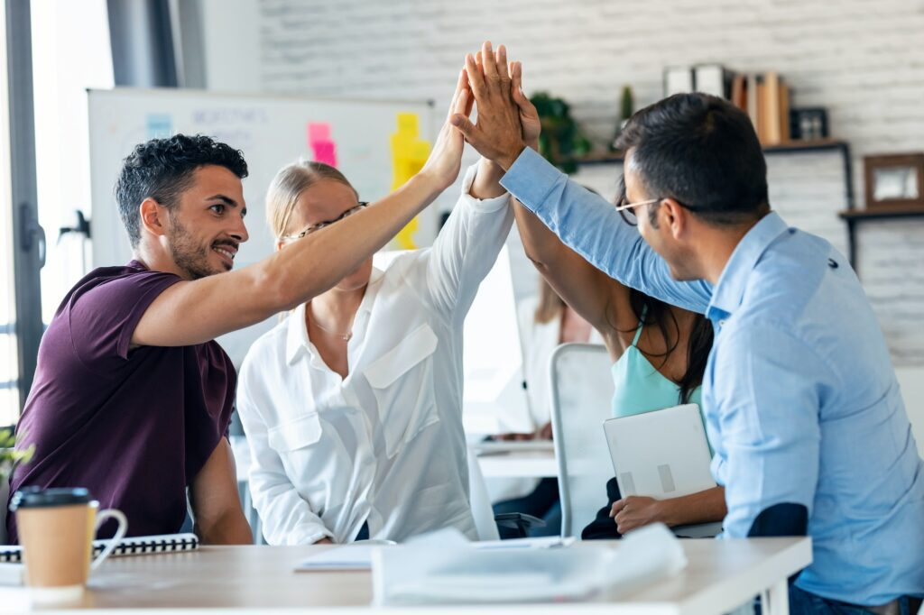 Successful business team celebrating good job while holding up their right hands on coworking place.