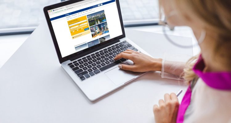cropped view of woman using laptop with booking website
